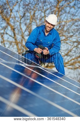 Portrait Of Man Worker In Blue Suit And Protective Helmet Installing Stand-alone Solar Photovoltaic
