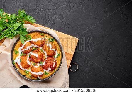 Malai Kofta Curry In Black Bowl At Dark Slate Background. Malai Kofta Is Indian Cuisine Dish With Po