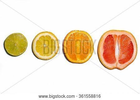 Slices And Halves Of Lemon, Lime, Orange And Grapefruit On A White Background. Multiple Kinds Of Cit