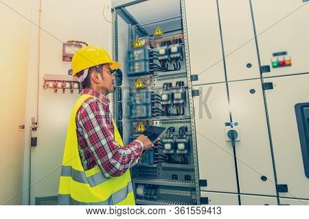 Engineer Standing In Front Of The Control Panel In The Control Room.