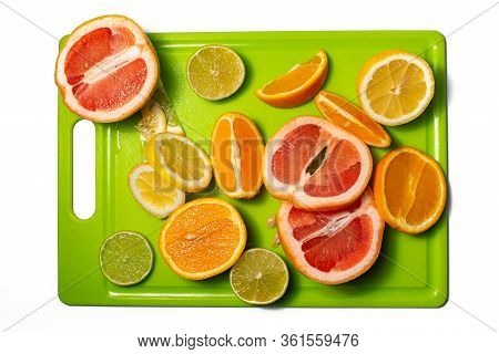 Slices And Halves Of Lemon, Lime, Orange And Grapefruit On A Green Chopping Board. Multiple Kinds Of