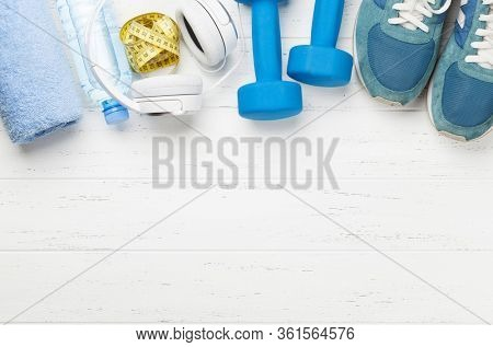 Fitness equipment on a wooden background. Top view flat lay with copy space for workout plan