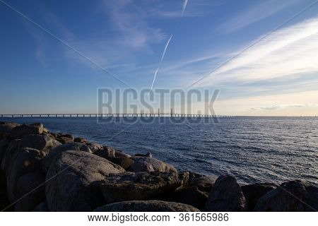 The Oresund Bridge Connects Sweden And Denmark. Seen From Rocky Coast In Summer Sunset.