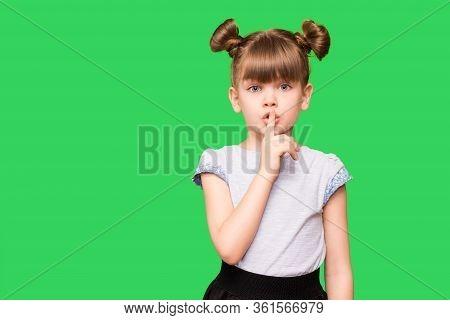 Emotional Child Girl Has Secret. Little Girl With Wonder Face Keeps Finger On Lips, Shows Silence Si