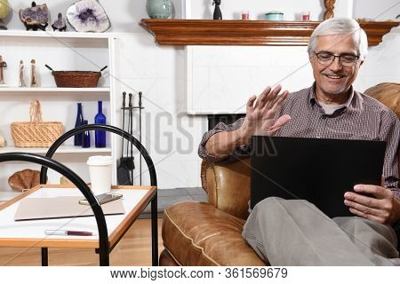 Senior man waving at his laptop screen as he video chats with family while under stay at home restrictions due to the COVID-19 pandemic.