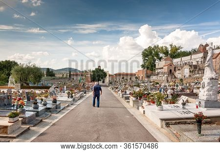 San Giminiano, Italy: Lonely Older Man Walking Past Tombstones Of Local Cemetary On 19 September 201