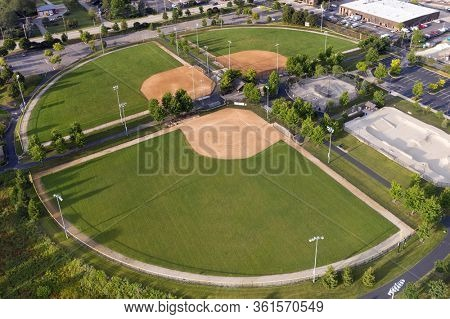 Aerial view of a multi-use playfield with baseball/softball diamonds and a skate park.
