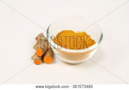 Turmeric Powder In A Glass Cup And Turmeric Roots Separately On A White Background, Used As A Tonic