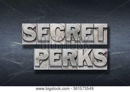 Secret Perks Phrase Made From Metallic Letterpress On Dark Jeans Background
