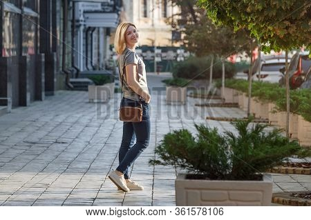 Blonde Young Woman Walking And Posing On Sunny Street. Woman Walking In The City At Sunset Alone. Li