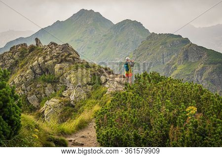 Tatra Mountains / Poland - July 2018: Woman Hiking, Standing On The Path In The Mountains And Taking
