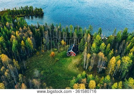 Aerial Top View Of Red Log Cabin Or Cottage With Sauna In Spring Forest By The Lake In Finland