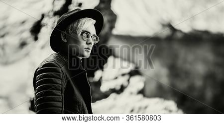 A monochrome portrait of a young fair-haired walking in open air. Casual fashion, beauty.