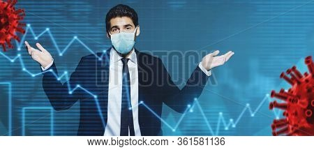 Coronavirus and business. A businessman in a medical mask makes a helpless gesture against the background of a coronavirus and stock charts. Copy space.