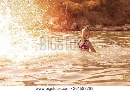 A Little Girl Splashing Around With A Lot Of Braggs In The Sea In The Rays Of The Setting Sun. Summe