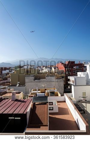 Charter Plane Leaving Tenerife Airport During Sunrise Seen From Roofs Of Traditional Houses With Mou