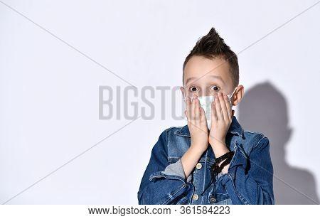 Blond Teenage Kid In Blue Denim Jacket, T-shirt. He Is In Medical Mask, Looking Panicked, Posing Iso
