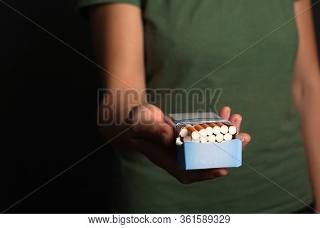 Hand Girl Holds  A Pack Of Cigarettes Suggests Making A Choice. Offer Nicotine, Tobacco.