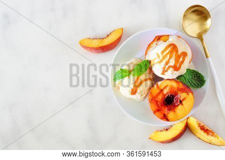 Delicios Grilled Peaches With Vanilla Ice Cream And Caramel Sauce. Top View Table Scene On A White M