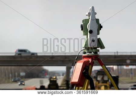 Geodetic Support Of Road Construction. In The Foreground, A Total Station On A Tripod, In The Backgr