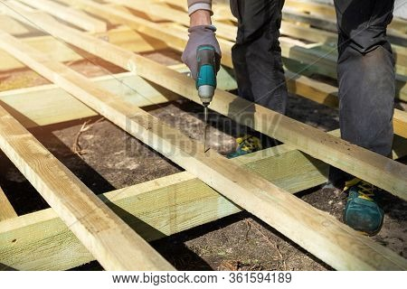 Man Building Wooden Frame For Patio Deck