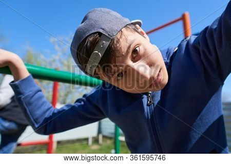 Teen portrait closeup, he stands by the outdoor workout equipment