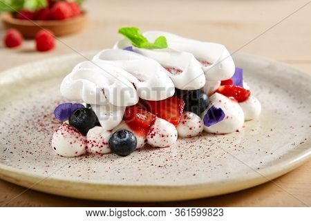 Pavlova dessert in white ceramic plate. Meringue cake, creamy bakery close up. Pastry with whipped cream, blueberry and strawberry. Gourmet appetizer with mint and violet petals decoration