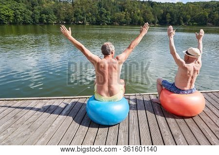 Two vital seniors with gymnastic ball do back exercises on the lake in summer