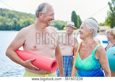 Happy senior couple as vital retiree with friends on vacation at the lake in summer