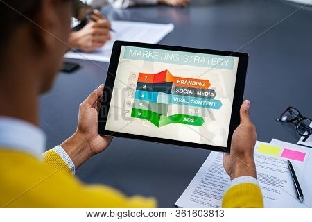 Close up of young man using digital tablet to study marketing strategy. African businessman studying business planning. Rear view of student holding tablet in hands and analyze business material.