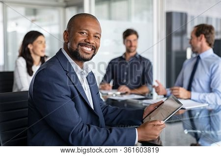 Proud mature black businessman smiling with colleagues sitting in a board room. Portrait of happy successful executive with team working in background while looking at camera during meeting. Success.