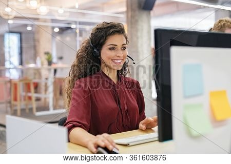 Customer support phone operator working at computer. Happy call center agent working on support hotline in office. Smiling call center agent in conversation with customer over headset.