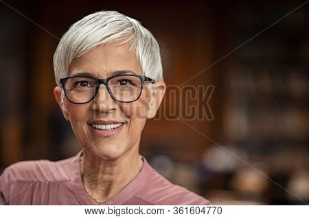 Portrait of beautiful senior woman looking at camera with copy space. Successful mature business woman wearing eyeglasses. Happy old professor in standing in college library with gray hair.