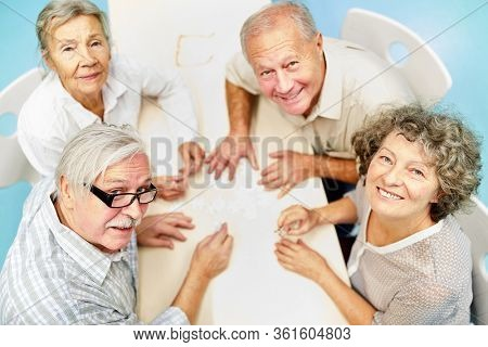 Group of seniors as friends in retirement home have fun playing puzzle
