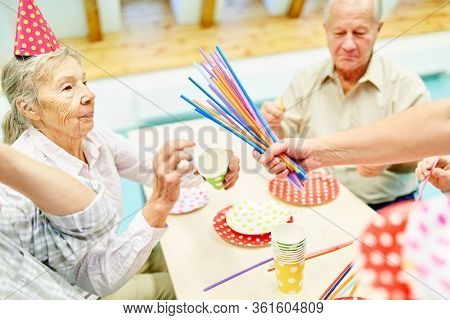 Senior citizens in a retirement home celebrate a party and are cared for by the caregiver
