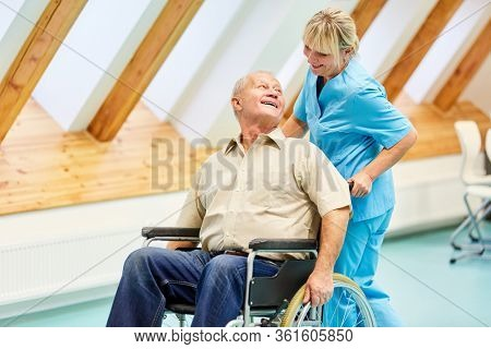 Happy senior in a wheelchair and his caring nurse in the nursing home
