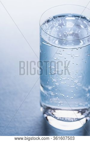 Cold Tonic Water In A Glass, Reflecting The Blue Color From The Background. Tonic Water With Bubbles