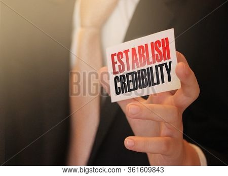 Businessman Putting A Card With Text Establish Credibility In The Pocket. Financial Business Concept