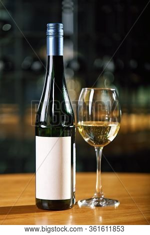 A Bottle Of Wine And Glasses On The Table, Against The Background Of A Wine Shakafa. Serving And Ser