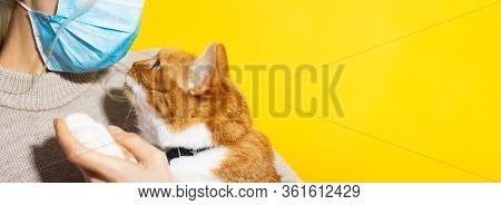Close-up Of Young Girl Wearing Medical Mask Against Coronavirus, Holding Red White Cat On Yellow Bac