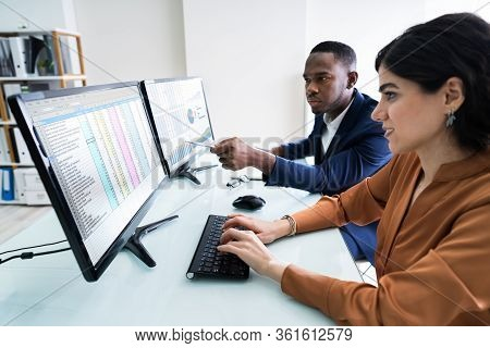 Male And Female Businesspeople Checking Spreadsheet On Computer Screen Over Desk