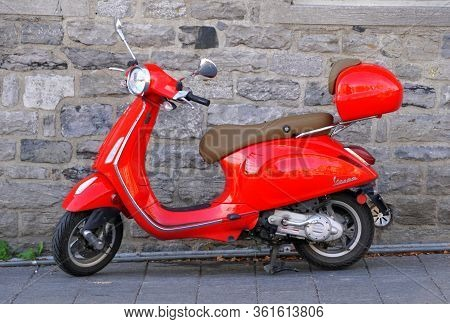 Montreal, Canada - October 27, 2019 - A Bright Red Vespa Scooter Parked On The Street