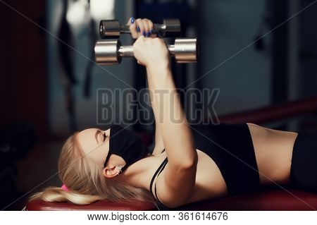 Young Girl In A Protective Mask Makes Wiring Dumbbells On A Bench. Protective Masks Against Virus In