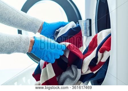 closeup of a young caucasian man, wearing blue latex gloves, putting clothes into the washing machine