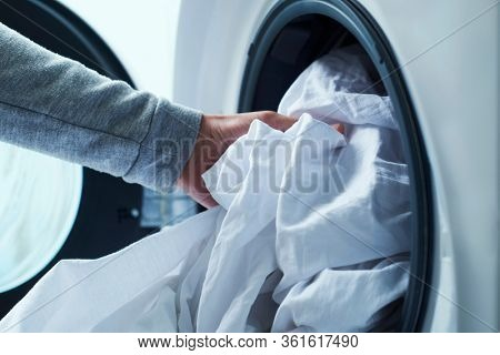 closeup of a young caucasian man putting white bed linen into the washing machine