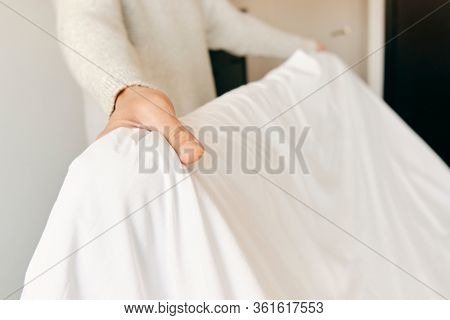 closeup of a young caucasian man making the bed with white bedsheets