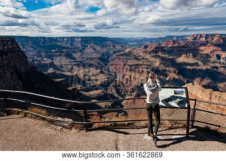 Grand Canyon, Arizona - November 6 2017: Young Woman Standing On The Edge Of Grand Canyon Taking A P