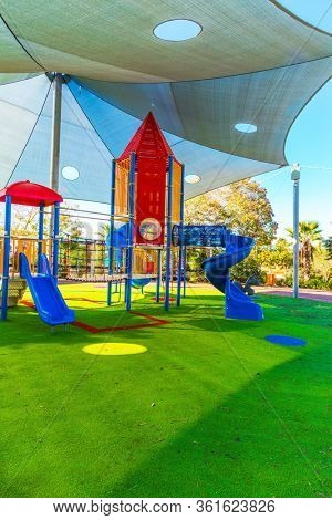 Great children 's playground. Spiral slide attraction with closed descent. Bright warm sunny morning. Concept of physical and mental development of children