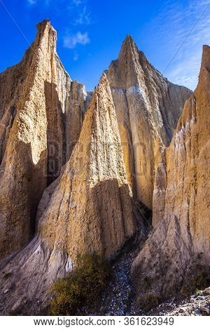 Jagged sharp pinnacles and ridges separated by narrow ravines. Clay Cliffs. New Zealand, South Island. Grandiose natural land formations. The concept of extreme, natural and photo tourism