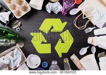 Top View Of Different Garbage Materials With Recycling Symbol On Black Background. Recycle, World En